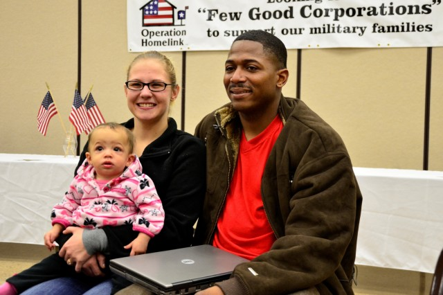 """FORT CAMPBELL, KY """" Mrs. Cassie Coley, Spc. Arthur Coley, a cargo specialist with the 101st Sustainment Brigade, 101st Airborne Division (Air Assault) and their daughter, eight-month-old Brianna Coley, sit together with their donated laptop from Operation Homelink at Fort Campbell's Family Resource Center, Jan. 26. """"I think this is a great thing done for my family by these really thoughtful people, said Mrs. Coley."""" (U.S. Army photo by Sgt. Alan Graziano, 3rd BCT PAO, 101st Abn. Div.)"""