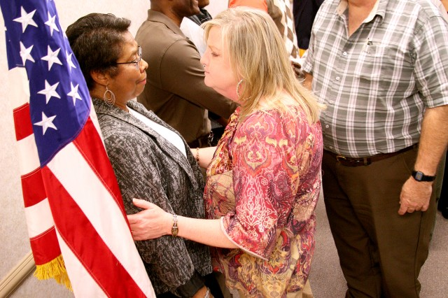 Belinda Walker, program analyst, U.S. Army Kwajalein Atoll/Reagan Test Site, U.S. Army Space and Missile Defense Command/Army Forces Strategic Command, and her family greet well-wishers following her retirement Jan. 23. Walker retires with 30 years of service.