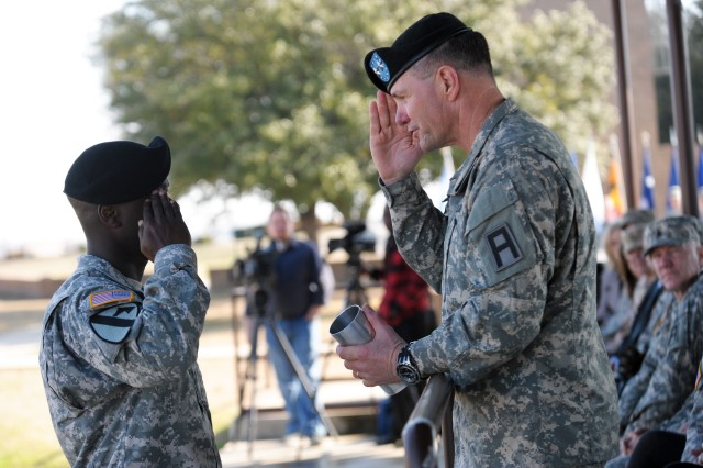 Maj. Gen. Perry Wiggins, right, outgoing Division West commanding general, receives a commemorative shell casing from Staff Sgt. Meyer Sherman during a change of command ceremony on Cameron Field near division headquarters at Fort Hood, Texas, Jan. 23. Maj. Gen. Warren Phipps Jr. assumed command of the division from Wiggins, who had led the unit since October 2011. Wiggins will go on to be the deputy commanding general of United States Army North (Fifth Army) at Fort Sam Houston, Texas. (Photo by Sgt. 1st Class Gail Braymen, Division West Public Affairs)
