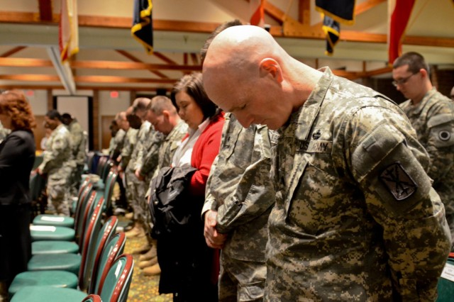 Soldiers, airmen and civilians from across Joint Base Lewis-McChord bow their heads in reverence for the opening invocation during the JBLM 2013 Dr. Martin Luther King Jr. Birthday Celebration at McChord Field Collocated Club, Jan. 22. (U.S. Army photo by Spc. Nathan Goodall, 17th Fires Brigade Public Affairs)