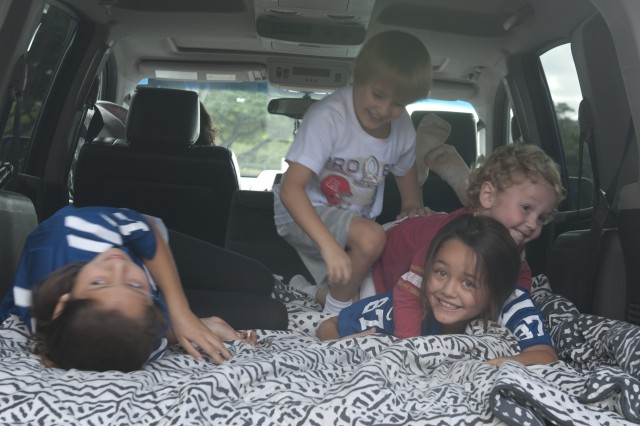 Children wrestle in the back of Sgt. 1st Class James Naber's, 45th Sustainment Brigade, 8th Theater Sustainment Command, a lifelong San Diego Chargers fan, SUV before the National Football League's 2013 Pro Bowl game at Aloha Stadium, Jan. 27.