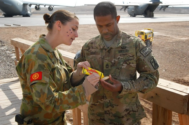 Australian Army Pvt. Tara Pavel explains the best way to eat Vegemite to Sgt. 1st Class Patrick Dove, 329th Transportation Detachment, 49th Joint Movement Control Battalion, at Multi National Base Tarin Kot, Afghanistan, on Australia Day, Jan. 26, 2013. Vegemite is an Australian food spread for sandwiches, toast, and biscuits, but for Americans is an acquired taste.