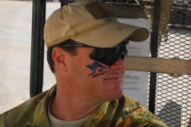 Australian Air Force Cpl. Aaron Beavington, Combined Team Uruzgan, takes a break from unloading cargo on the flightline at Multi National Base Tarin Kot, Afghanistan, on Australia Day, Jan. 26, 2013. Members of the Australian Defence Force celebrated Australia Day by wearing unique outfits, face tattoos, and decorative memorabilia.