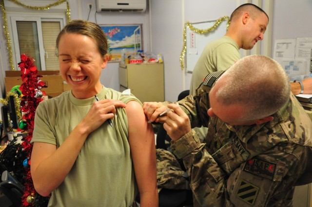 U.S. Navy Chief Hospital Corpsman (Surface Warfare/Air Warfare) Jay Thrailkill gives Lt. jg. Jessica Friddle a flu shot in Kandahar City, Afghanistan, Dec. 14. Thrailkill has participated in more than half of the mounted combat missions with Kandahar Provincial Reconstruction Team. (U.S. Army Photo by Staff Sgt. Jeff Neff)