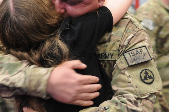 Sgt. Erick Lane embraces his wife during the 3d ESC's redeployment ceremony at the Natcher Physical Fitness Center, January 12, 2013. The 3d ESC was deployed for a nine month tour in Afghanistan.