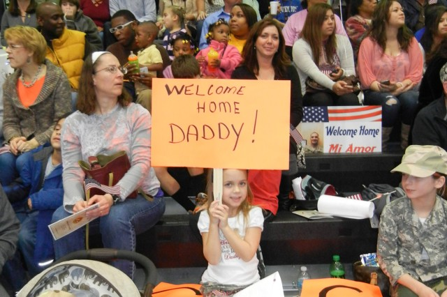 Taylor Garrison holds up a welcome home sign for her father, Maj. Shane Garrison, during the 3d ESC redeployment ceremony at the Natcher Physical Fitness Center, January 12th, 2013.