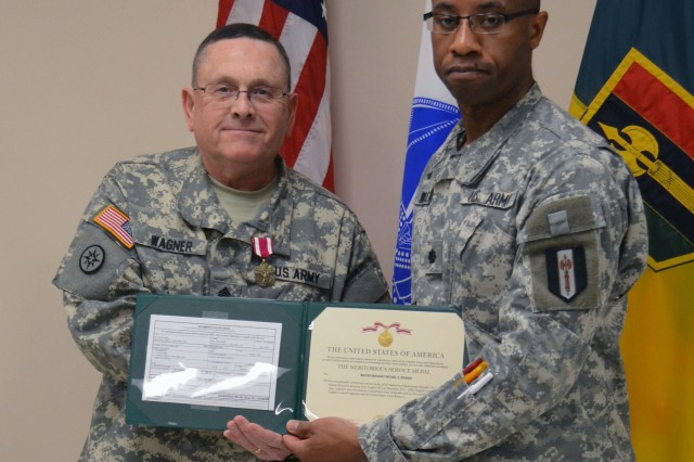 Lt. Col. Philmore Williams, deputy commander of 302nd Maneuver Enhancement Brigade, 412th Theater Engineer Command, presents the Meritorious Service Medal to Master Sgt. Michael Wagner during his retirement ceremony held at the 302nd headquarters in Chicopee, Mass.  Wagner received the award for 34 years of honorable service to the unit, Army and country.
