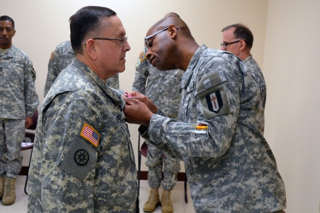 Lt. Col. Philmore Williams, deputy commander of 302nd Maneuver Enhancement Brigade, 412th Theater Engineer Command, pins the Meritorious Service Medal on Master Sgt. Michael Wagner during his retirement ceremony held at the 302nd headquarters in Chicopee, Mass.  Wagner received the award for 34 years of dedication and service to the unit, Army and country.