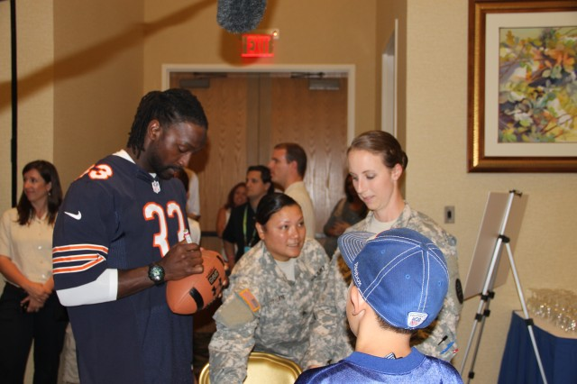 "SCHOFIELD BARRACKS, Hawaii "" Charles Tillman, corner back for the Chicago Bears, signs a football for an excited fan at a wounded warrior luncheon at the Nehelani, here, Jan. 24.  Purple Heart recipients and combat-wounded Soldiers from the Warrior Transition Battalion, and the 25th Infantry Division's 2nd Brigade Combat Team, 3rd Brigade Combat Team and 25th Combat Aviation Brigade were hand picked and invited to attend the luncheon.  Tillman is on island for the 2013 Pro Bowl, the all-star game for the National Football League. The match up pits the NFL's American Football Conference's best against the National Football Conference's best. It has been played at Honolulu's Aloha stadium since 1970, with the exception of 2009, when it was played in Miami.  Joining Tillman were Victor Cruz (New York Giants wide receiver), Marshawn Lynch (Seattle Seahawks running back), Jason Witten (Dallas Cowboys tight end), Doug Martin (Tampa Bay Buccaneers running back), and Julio Jones (Atlanta Falcons wide receiver)."