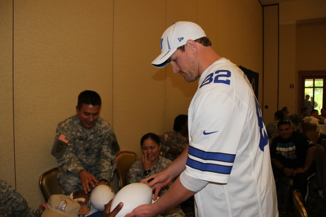 "SCHOFIELD BARRACKS, Hawaii "" Jason Witten, tight end of the Dallas Cowboys, gets ready to sign a football for a fan at a wounded warrior luncheon at the Nehelani, here, Jan. 24.  Purple Heart recipients and combat-wounded Soldiers from the Warrior Transition Battalion, and the 25th Infantry Division's 2nd Brigade Combat Team, 3rd Brigade Combat Team and 25th Combat Aviation Brigade were hand picked and invited to attend the luncheon.  Witten is on island for the 2013 Pro Bowl, the all-star game for the National Football League. The match up pits the NFL's American Football Conference's best against the National Football Conference's best. It has been played at Honolulu's Aloha stadium since 1970, with the exception of 2009, when it was played in Miami.  Joining Witten were Charles Tillman (Chicago Bears corner back), Victor Cruz (New York Giants wide receiver), Marshawn Lynch (Seattle Seahawks running back), Doug Martin (Tampa Bay Buccaneers running back), and Julio Jones (Atlanta Falcons wide receiver)."