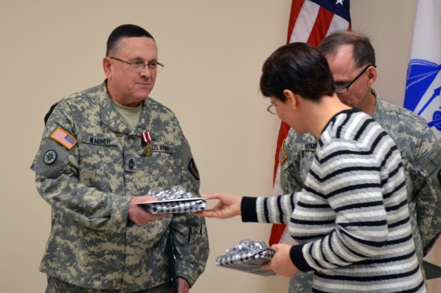 Paula Lupien, Staff Administrative Assistant with 302nd Maneuver Enhancement Brigade, 412th Theater Engineer Command, presents unit parting gifts to Master Sgt. Michael Wagner, as token of appreciation for outstanding service and sacrifice, during his retirement ceremony held at the 302nd headquarters in Chicopee, Mass.