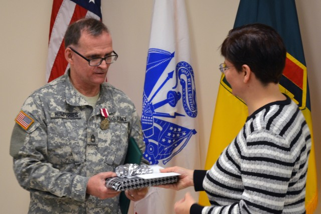 Paula Lupien, Staff Administrative Assistant with 302nd Maneuver Enhancement Brigade, 412th Theater Engineer Command, presents unit parting gifts to Sgt. 1st Class Steven Humphries, as token of appreciation for outstanding service and sacrifice, during his retirement ceremony held at the 302nd headquarters in Chicopee, Mass.