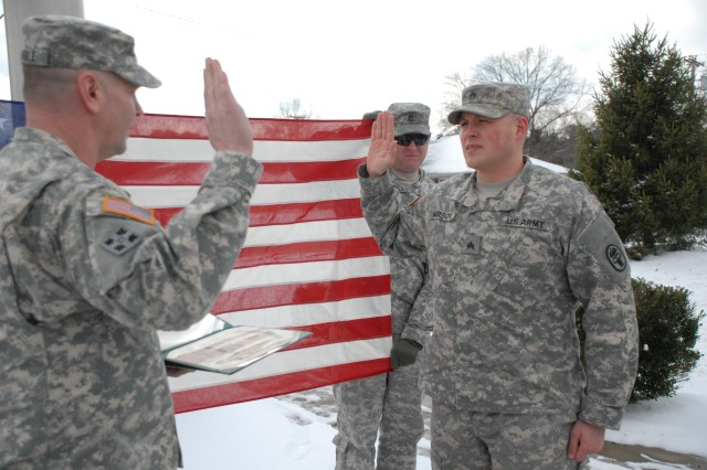 Lt. Col. Peter E. Dargle administers the reenlistment oath with SGT Christopher J. Watson II (Foreground) as CSM Keith L. Whitcomb (Holding US Flag) and family and friends support this Army Strong NCO retention reenlistment.