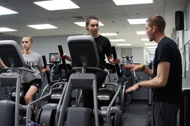 race Glen receives instruction from Mike Cronin, a West Point firefighter and fitness instructor, on the proper use of the elliptical machine. On completion of the program, teens 13-15 years of age can use the fitness center without parental supervision.