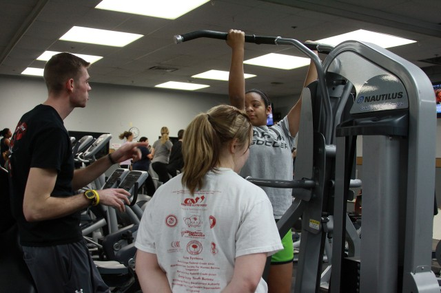 Mike Cronin, West Point firefighter and fitness trainer, teaches Gabriela Huggins, 13, how to use a strength training machine at the FMWR Fitness Center Jan. 25.