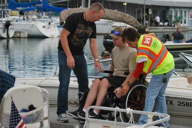 Two men help a wounded warrior get into a boat during Take a Warrior Fishing Day in Fort Worth, Texas. Take a Wounder Warrior Fishing is just one project that the Corps of Engineers will be partnering with Bass Pro as part of a Memorandum of Understanding between to two organizations to promote water and boating safety and improve fish habitats.