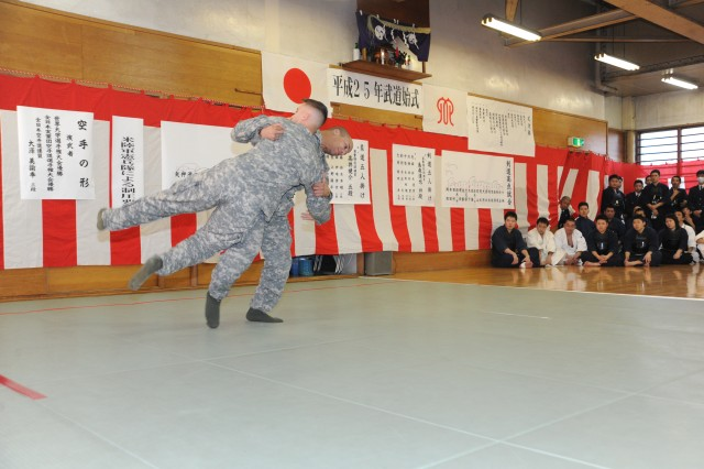 Staff Sgt. Matthew Prout, assigned to the 88th Military Police Detachment at Camp Zama, demonstrates modern Army combatives to Japanese police officers during the annual New Year's martial arts demonstration held Jan. 22 at the Sagamihara South Police Station.