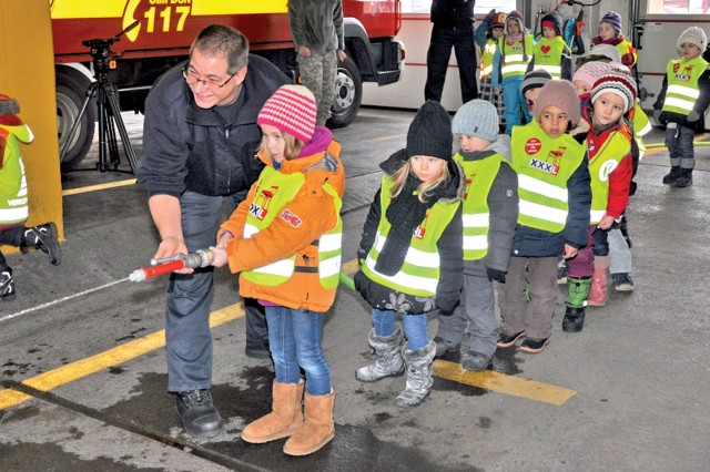 U.S. Army Garrison Wiesbaden firefighter Bjoern Christ helps youngsters aim a fire hose during their visit to the Clay Kaserne Fire Department. The students of the Obermayr school learned about fire safety, and one of the highlights was a ride in a firetruck.