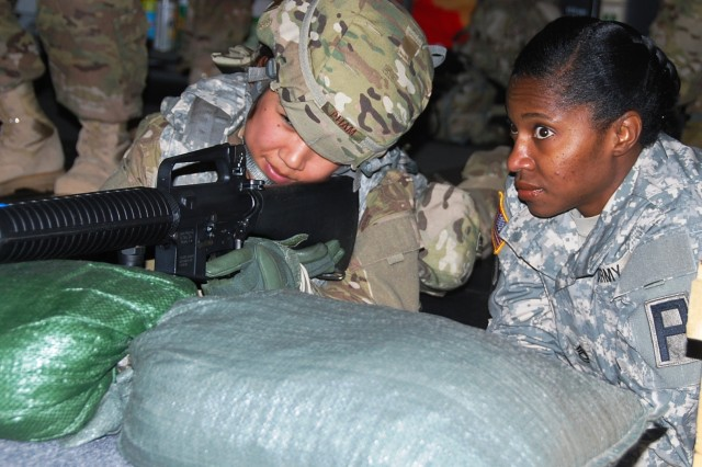 Sgt. 1st Class Katura Moorer, trainer/mentor with the 174th Infantry Brigade, First Army Division East, discusses shot placement and grouping with Staff Sgt. Stephanie Pham, from San Francisco, Calif., who is heading to Bagram Airfield, Afghanistan in February to assist an Explosive Ordinance Disposal team.