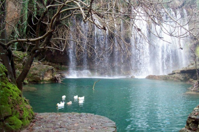 A waterfall cascades amidst the peaceful surroundings of Kursunlu Waterfall Nature Park.