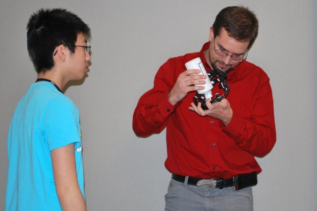 Dr. Brent Lance, Human Research and Engineering Directorate, prepares the Emotiv Epoc for use by moistening the electodes with saline. Also shown is Tarit Jitsuriya, an 11th grader from Bel Air High School.