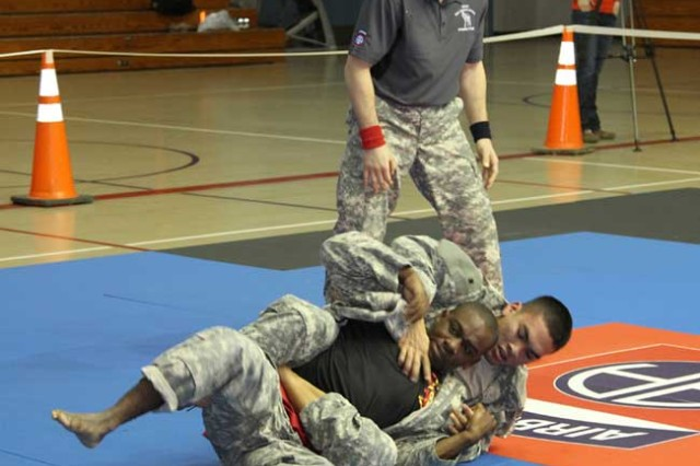 Private Jodoniss Edwards (red belt), Headquarters and Headquarters Battery, 2nd Battalion, 319th Field Artillery Regiment, and Pfc. Jesse Sablan, Headquarters and Headquarters Troop, 1st Squadron, 38th Cavalry Regiment compete in the Fort Bragg Combatives Tournament at Ritz-Epps Physical Fitness Center, Jan. 18, fighting under the standard rules. (Photo by Sgt. Amie J. McMillan, 10th PCH PAO)