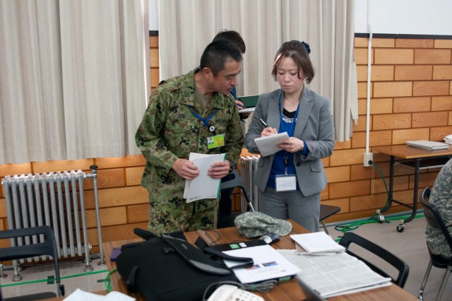 Lt. Col. Noritaka Ito, Japan Ground Self Defense Force liaison officer to U.S. Army Japan, pays close attention to USARJ and I Corps (Forward) translator/interpreter Mayuko Omoto as she provides translation during the Sapporo Epicenter humanitarian assistance and disaster relief exercise, which was conducted Jan. 23-27, 2913, at Camp Sapporo, Hokkaido, Japan.