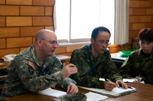During a round table discussion, deployable assessment team leader Col. Frank Clark and Northern Army Japan Ground Self Defense Force plans officers discuss details of exercise Sapporo Epicenter during a round table meeting regarding a humanitarian assistance and disaster relief exercise at Camp Sapporo, Hokkaido, Jan. 23-27, 2013.