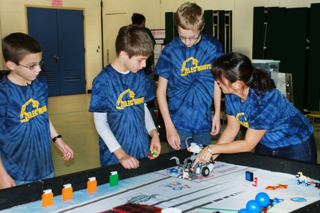 Electrobots coach Virginia To discusses robot strategy with (from left) Sam Boin, George Houzouris and Aaron Boin, at a FIRST LEGO League competition, Jan. 26, 2013. Seven students, sponsored by U.S. Army Research Laboratory and Aberdeen Proving Ground, Md., took top honors at the FIRST LEGO League competition at the University of Delaware, Jan. 26.