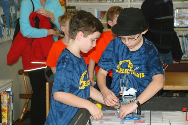Tommy Sukiennik (left) and Sam Boin change the robot's attachments during a practice run at a FIRST LEGO League competition, Jan. 26, 2013. Seven students, sponsored by U.S. Army Research Laboratory and Aberdeen Proving Ground, Md., took top honors at the FIRST LEGO League competition at the University of Delaware, Jan. 26.