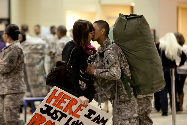"Pfc. James Solima, 203rd Brigade Support Battalion, kisses his wife Feb. 1 at Freedom Hall after returning with his unit from a seven-month deployment to Kuwait. The sign reads ""Here I am, just like I promised."""