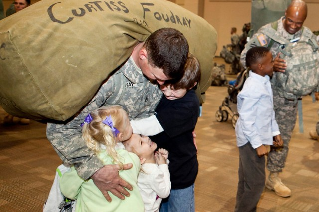 Staff Sgt. Curtis Foudray hugs his children, Alexis, Addison and Andrew. There were smiles all around for the hundreds of family members who waited not-so-patiently as the plane landed and the troops disembarked Feb. 1.