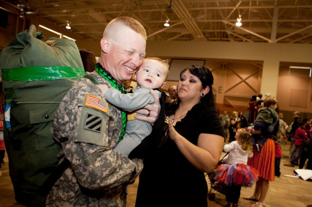 Sgt. David Bunnell hugs his 7-month-old son, Jagger, at the welcome home ceremony Feb. 1.