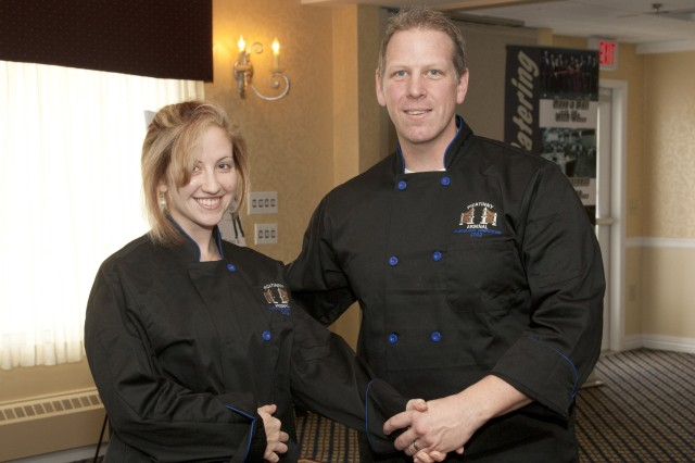 PICATINNY ARSENAL, N.J. - Scott Miller (right), Assistant Food, Beverage and Entertainment Director, presents Alicia Morante with a Picatinny Master chef jacket after winning the first round of the installation's Master Chef competition last year.