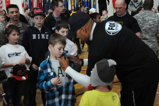David Justice signs 10-year-old Cristopher Isaac's shirt as his brother, Jace, 5, looks on in the foreground following the Fox Sports wiffleball game at the Grafenwoehr Physical Fitness Center, Feb. 6.