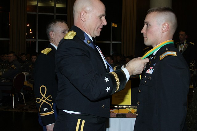 Maj. Gen. H.R. McMaster, commanding general of the U.S. Army Maneuver Center of Excellence and guest speaker at the third annual Maneuver Ball Feb. 1 at the West Point Club, places the Noble Patron Saint of Armor Award on Maj. Dallas Cheatham, instructor in the Department of Military Instruction. The United States Armor Association awards its Noble Patron of Armor Award to individuals who have contributed considerably to the operational success of armor and cavalry organizations. The award is bestowed upon civilians or servicemembers who are not branched armor.