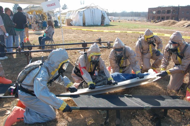During the Vibrant Response training exercise, members of the Ohio Chemical Enhanced Force Protection Package slide an injured woman onto a stretcher. After a simulated nuclear attack, the decontamination team was tasked with extracting people from a building within the contaminated area.