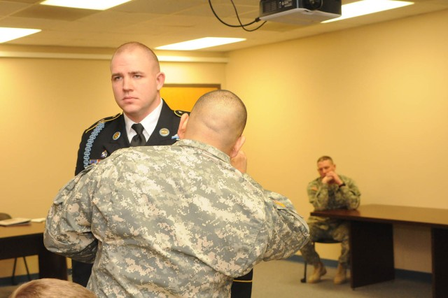 Staff Sgt. Pedro Leos, Sgt. Audie Murphy Club secretary, checks Sgt. 1st Class Surya Hays' uniform during the organization's first board. Hays was the only SAMC candidate to be selected for induction in to the club.