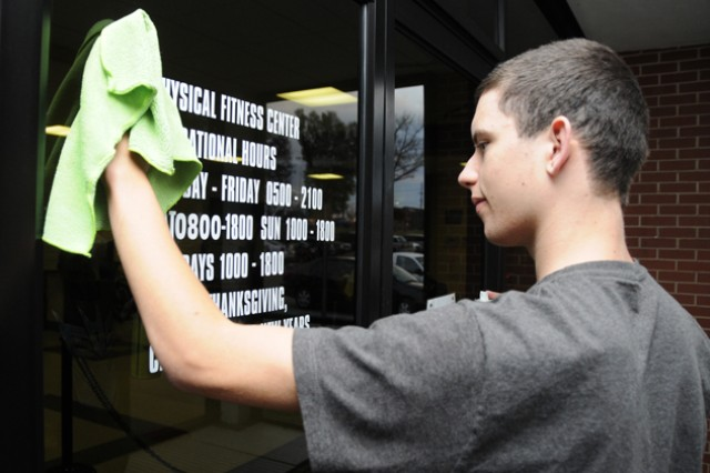 Justin Ritchie, 18, cleans the windows at the physical fitness facility on Andrews Avenue Feb. 4 as part of the Hired! Apprenticeship Program.