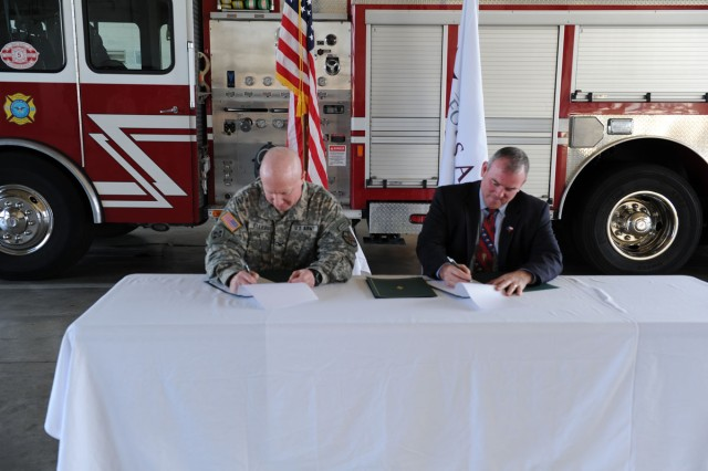 Fort Hood Garrison Commander Col. Matt Elledge joins Texas A&M Forest Service Director Tom Bogguss in signing three copies of the Mutual Aid Agreement at Fort Hood, Texas, Feb. 4. The agreement will provide more rapid and efficient response to wild land fires as well as open up reciprocal training opportunities between the agencies. (U.S. Army photo by Heather Graham-Ashley, III Corps and Fort Hood Public Affairs)