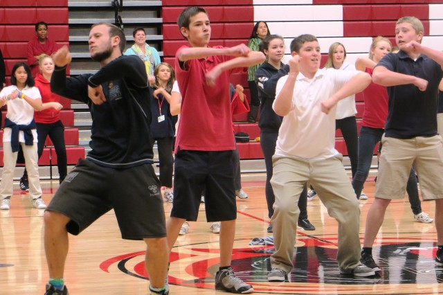 From left, Maos Luovigsen of the National Danish Performance Team and Colonel Smith Middle School eighth-grade students Lat Bowen, 13; Jonathan Shedio, 13; and Hunter Henry, 14, have fun while exercising during a workshop at the school on Tuesday. In addition to performances at each venue visited, members of the NDPT present informal workshops for youth and adults in order to promote fitness and healthful lifestyles.