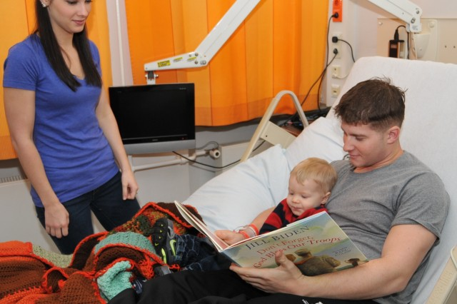 Spc. Michael Allison reads to his son Logan from a book given to him by Jill Biden, Ph.D., during a Feb. 3, 2013, visit by Vice President Joe Biden and Mrs. Biden, with staff and patients at Landstuhl Regional Medical Center, Germany. Looking on is his wife Rhea Allison.