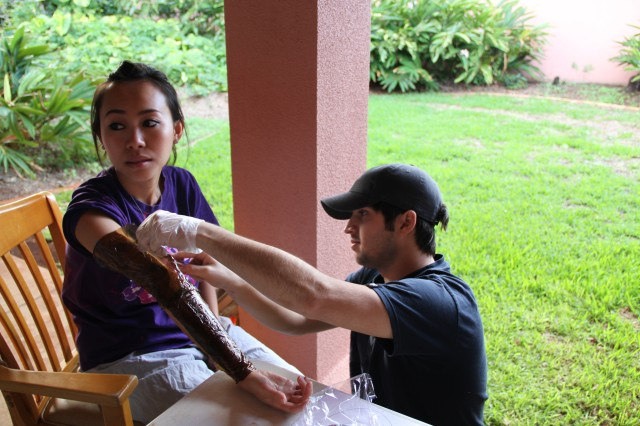 HONOLULU -- Stephen Goodson (right), volunteer moulage artist, applies a fake burn to Lina La, nursing student, University of Hawaii-Manoa, in preparation of a mass casualty exercise, Feb. 5, here. The mock incident was an explosion in the Center for Aging's kitchen and involved treating casualties on site and then evacuating them to Tripler Army Medical Center's emergency room.