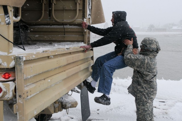 Pvt. First Class Juan Jimenez, of the 1182 Forward Support Company, helps Robert Wells, of the Kingston Police, into a 2 1/2 ton truck after Wells was stranded by flood waters caused by winter storm Nemo.