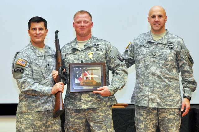 Sgt. 1st Class Geoffrey Applegate (center), California National Guard, took home the top prize at the 2013 U.S. Army Small Arms Championship after winning the overall individual championship. He is presented a Secretary of the Army M-1 Garand Trophy Rifle by Lt. Col. Don King, commander, U.S. Army Marksmanship Unit (left), and Col. Michael W. Rauhut, commander, 197th Infantry Brigade. Besides winning his first championship, Applegate was also a member of the overall team champions and earned his distinguished rifleman's badge. Sgt. 1st Class John Buol finished in second place and four-time defending champion Master Sgt. Russell Moore came in third.
