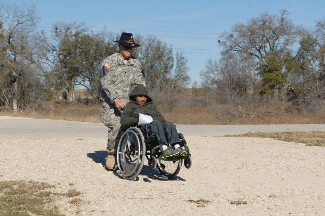 "San Francisco native Lt. Col. Jay Miseli (left), the commander for 1st Squadron, 7th ""Garryowen"" Regiment, 1st Brigade Combat Team, 1st Cavalry Division, wheels 9-year-old Houston native Neil Sawh through the Garryowen Games obstacle course, Feb. 8, 2013, at a Fort Hood, Texas, range. Sawh was diagnosed with muscular dystrophy at age 7 and wants to be a Soldier."