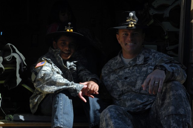 "Nine-year-old Houston native Neil Sawh sits with San Francisco native Lt. Col. Jay Miseli (right), the commander for 1st Squadron, 7th ""Garryowen"" Regiment, 1st Brigade Combat Team, 1st Cavalry Division, in the back of an M3A3 Cavalry Fighting Vehicle, Feb. 8, 2013, at the squadron headquarters at Fort Hood, Texas. Sawh, who has been diagnosed with muscular dystrophy, spent the day with Garryowen. Miseli appointed Sawh deputy squadron commander for the day."