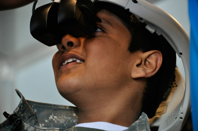 Nine-year-old Houston native Neil Sawh dons a helmet with a display screen that allows him to identify and engage enemy targets on the U.S. Army Mission Support Battalion's Special Operations Semi ground mobility vehicle, Feb. 8, 2013, at the 1st Cavalry Division Museum at Fort Hood, Texas. Sawh served as the gunner on the GMV.