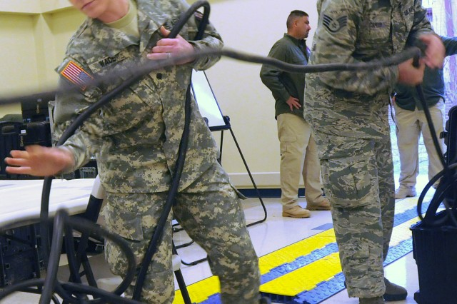 CAMP BULLIS, Texas - Spc. Lora Wade (left) and Air Force Staff Sgt. Samuel Carter uncoil power cables Feb. 4 during the setup of Joint Task Force-51's Joint Operations Center. Wade, a native of Lee, Mass., augmented JTF-51's J3 section during the exercise. She is assigned to the 302nd Maneuver Enhancement Brigade, which is based out of Westover Air Force Base, Mass. Carter, a native of Oklahoma City, serves as a staff weather operations forecaster with the 3rd Weather Squadron out of Fort Hood.  (U.S. Army photo by Sgt. 1st Class Christopher DeHart, Army North PAO)