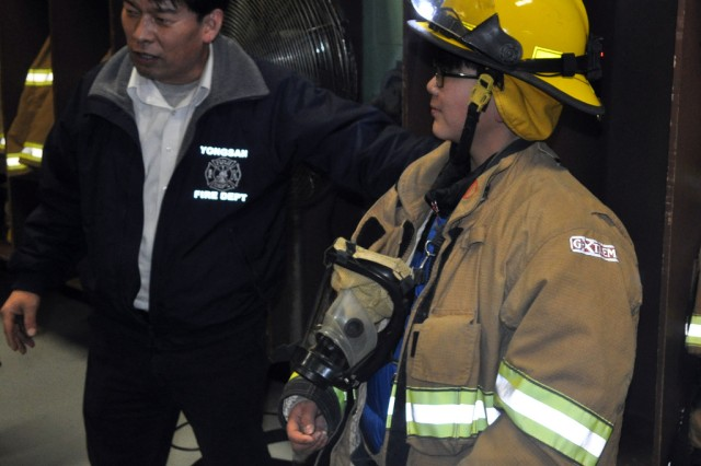 A camp participant with the Keukdong University Global Leadership Development Program wears a firefighters' uniform during an on-site field trip in Yongsan, as a part of experiencing a firefighters' daily life, Feb. 1. (U.S. Army photo by Pfc. Jung Jihoon)